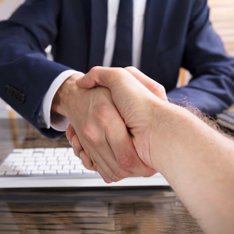 Two men in a meeting shaking hands as a result of an agreement.
